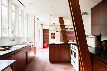 Mid-century kitchen with white walls, building-in shelving, wood cabinets and beams