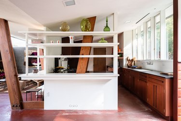 A mid-century home with maroon floors, built-in shelves, wood cabinets and beams