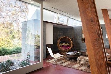 Mid-century living room with large glass windows, wood beams, and maroon floors