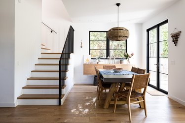 Dining room with white walls, wood furniture and flooring with staircase