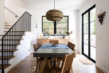 Dining room with white walls and wood floors with large windows and a staircase