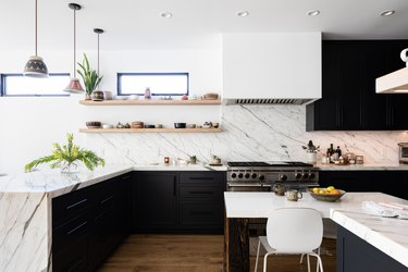 White kitchen with granite countertop and black cabinets on hardwood floor