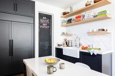 White-walled Kitchen with gray cabinets, white dining table and wood shelving