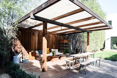eco-friendly patio with a wood pergola with wood flooring, dining bench and sofa seating