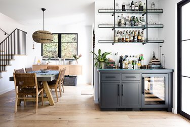 A dining room with wood floors and a gray cabinet Contemporary Bar with shelving