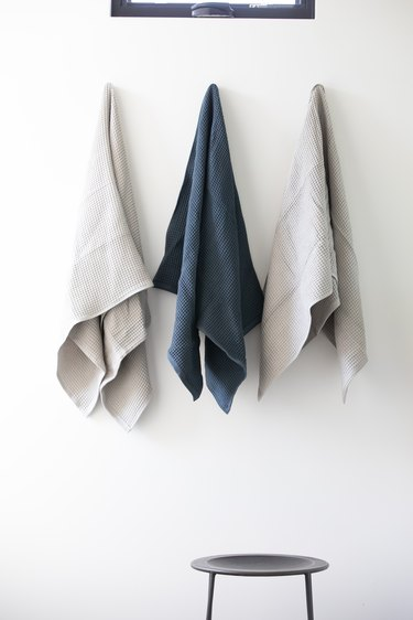 Gray and white towels hanging from white bathroom wall over a stool