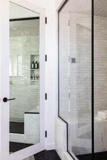 Bathroom door with a full-length mirror and a glass door shower
