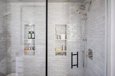 Glass door shower with gray wall tiles and shower niches