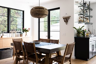 A dining room with a wicker globe pendant light, large windows and a bar