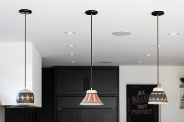 Pendant lights with multi-colored shades in a white-walled kitchen