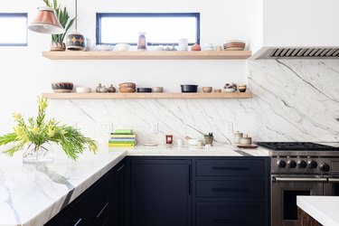 White granite walled kitchen with black cabinets, plants and wood shelves