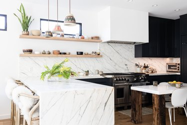 White walled kitchen with dark gray cabinets, plants and wood floors