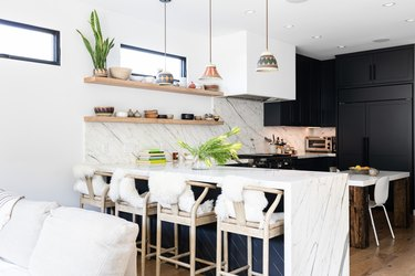 White walled kitchen with granite counters, white chairs, and dark gray cabinets