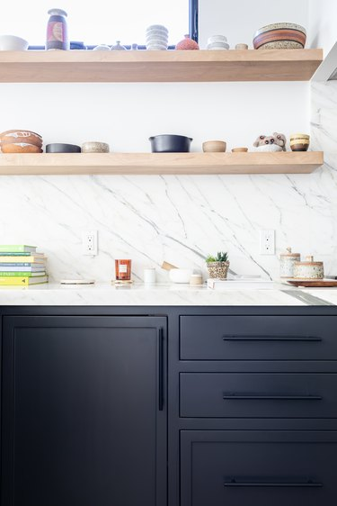 White walled kitchen with dark gray cabinets and wood shelving with pottery