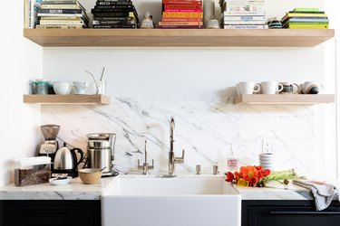 White granite wall of a kitchen with white sink and wood shelving with books