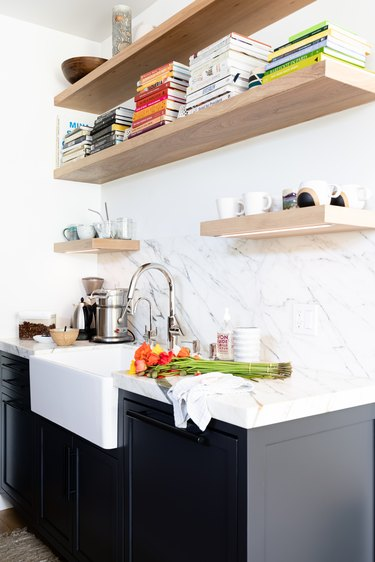 White walled kitchen with gray cabinets, granite countertops and wood shelving