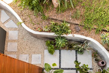 A curved white patio wall with plants and vases and a concrete path
