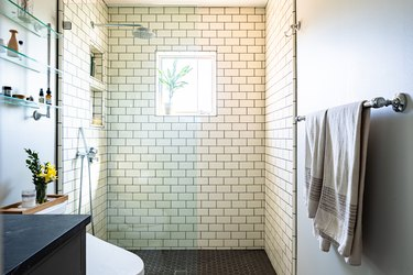A white tiled shower with glass doors in a bathroom with black floors