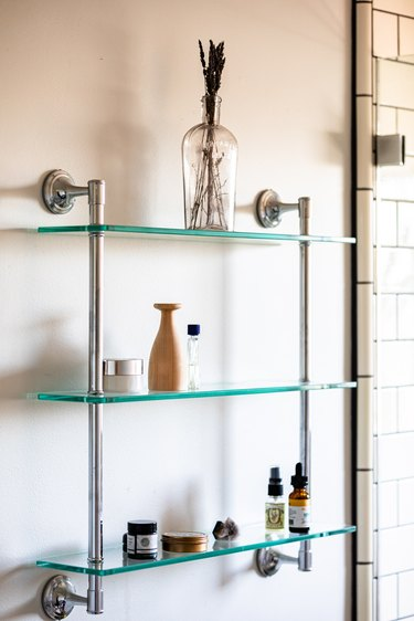 A glass shelving unit attached to a white bathroom wall