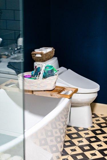 White-black geometric bathroom floor with a white bathtub and toilet