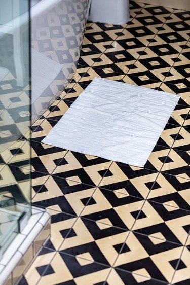 white bathmat on black and yellow tiled bathroom floor