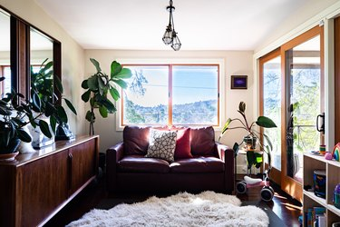 A boho style living room with pillows and fur rug with plants and wood furniture