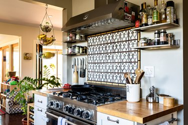 A kitchen with white cabinets with wood countertops and tile backsplash