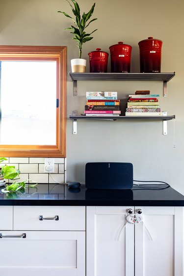 A kitchen with black countertops, white cabinets and metal shelving