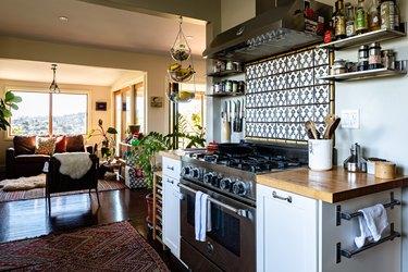 Kitchen with gas range, tile backsplash, wood counters, shelves.