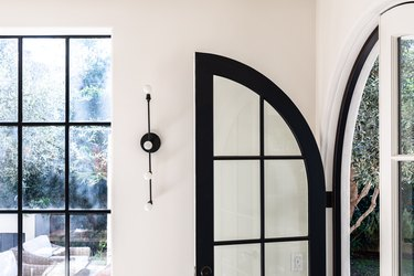 A black French door in a room with white walls and a wall sconce