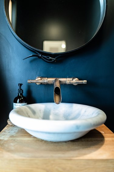 A white sink basin with a contemporary faucet in a bathroom with blue walls