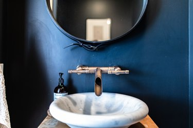A white sink basin with a contemporary faucet with a blue bathroom wall