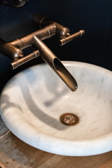 A white sink basin with an industrial style faucet