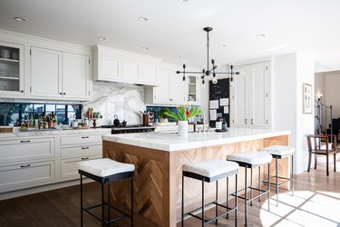 A kitchen with white cabinets, contemporary light fixture and wood kitchen island