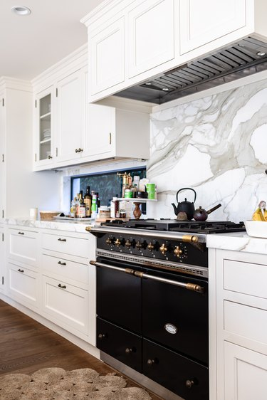 black stove with gas stovetop and marble backsplash