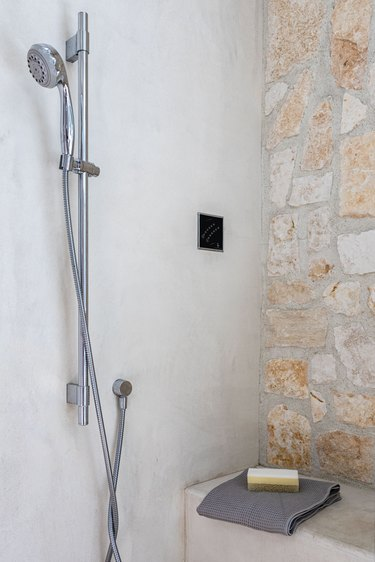 A shower with a rock accent wall