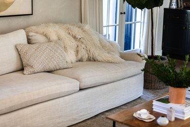 A white living room sofa with matching pillow and a white fur blanket by a coffee table