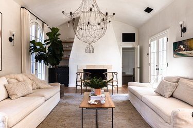 A white walled living room with white sofas and a chandelier