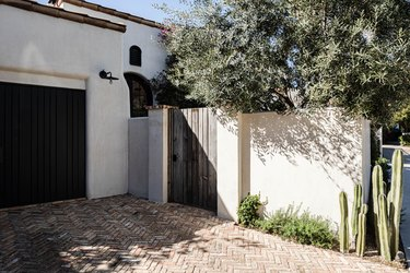 White Mediterranean style home with terra-cotta roofing and a wood door