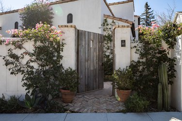 Mediterranean home with a terra-cotta roof and wood door with flower bushes