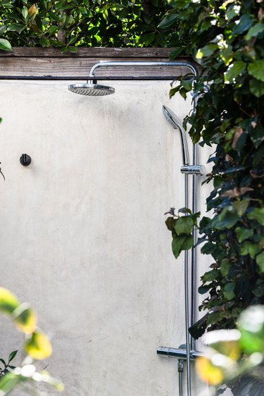An outdoor shower by a white wall surrounded by ivy
