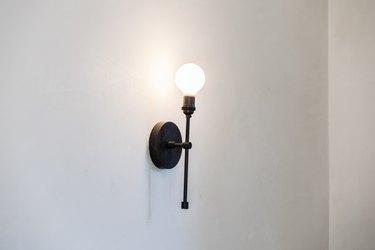 A globe light sconce on a white wall