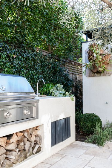 An outdoor patio grill with firewood and a sink with plants