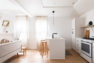 modern white open plan kitchen with white linen voiles