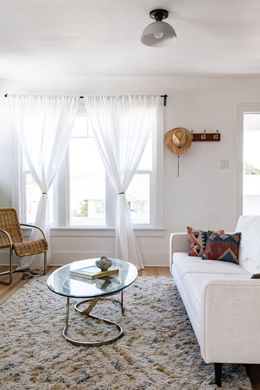 living room with sheer curtains in front of windows