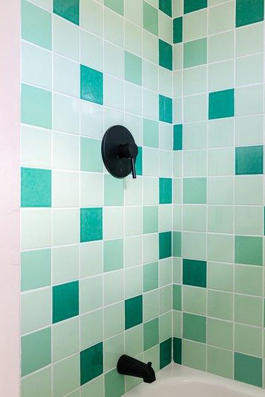 Multiple shades of green ceramic tile in bathroom, black faucet.