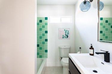 white toilet, green square shower tile, wood vanity with white ceramic wink, blue light fixture, white walls, tan tile floor