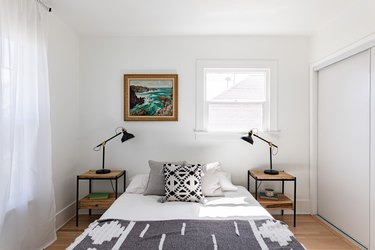 Bedroom with boho pillow and blanket, two side tables with black lamps