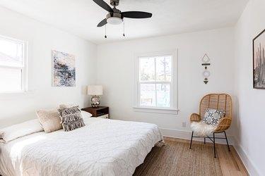 White bedroom with black ceiling light fan