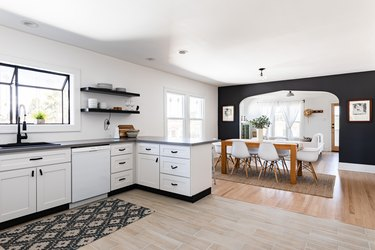 A white kitchen with white-black cabinets and a dining room with wood floors